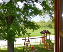 Pohled z okna pokoje penzionu na lípy směrem k Lipnu